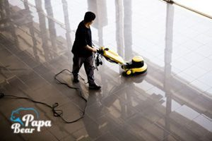 After builders cleaner cleaning a floor with professional machine